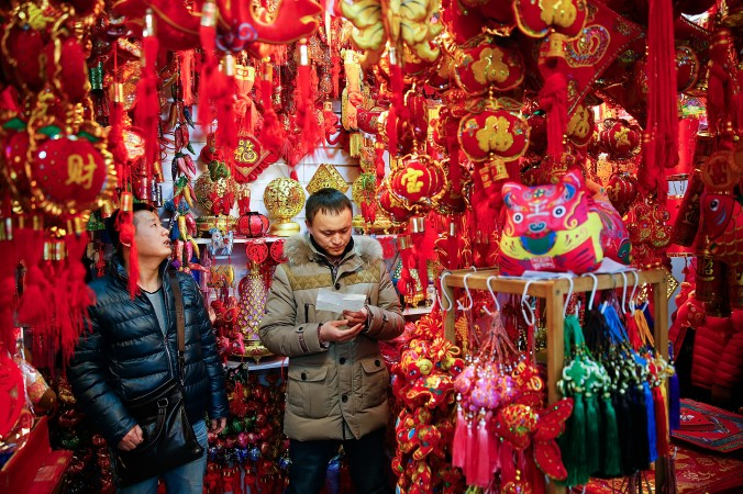 Китайцы покупают украшения для празднования Нового года по лунному календарю, Пекин, 12 февраля 2015 г. Фото: Lintao Zhang/Getty Images