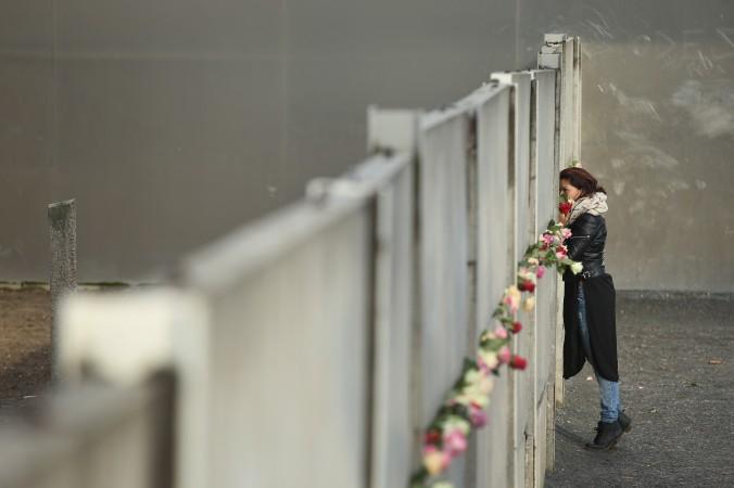 Женщина возлагает цветы на руины Берлинской стены 9 ноября 2015 года, в день 26-й годовщины её сноса. С 1961 по 1989 г. стена отделяла немцев на восточной территории от демократического Запада. Берлинская стена стала символом «холодной войны» и советского коммунизма. Фото: Sean Gallup/Getty Images