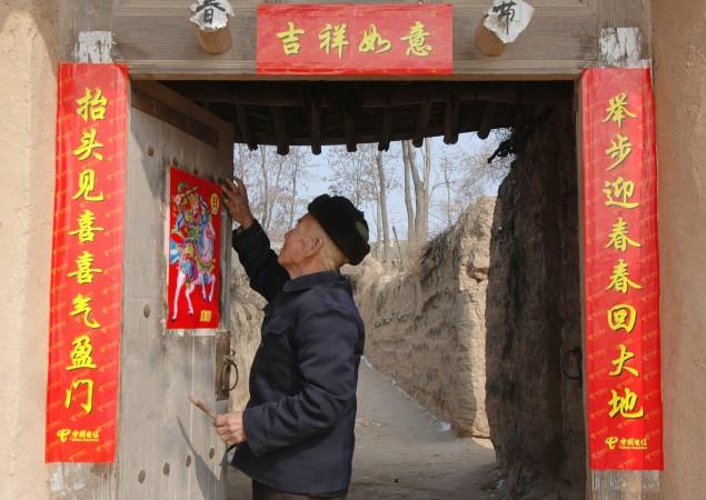 Пожилой человек проходит мимо новогодних куплетов на дверях, район Фу, провинция Шаньси 7 февраля 2005 г. Фото: China Photos/Getty Image