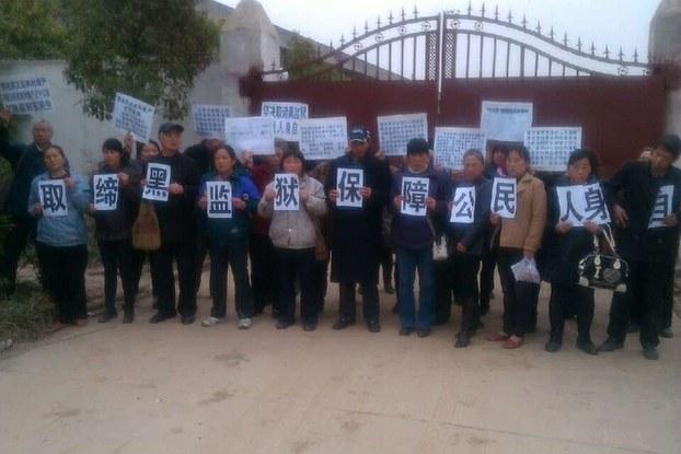 На фоне ворот одной из «чёрных тюрем» Китая петиционеры держат листки с требованием закрыть «чёрные тюрьмы» и защитить личную свободу граждан. Фото: epochtimes.com
