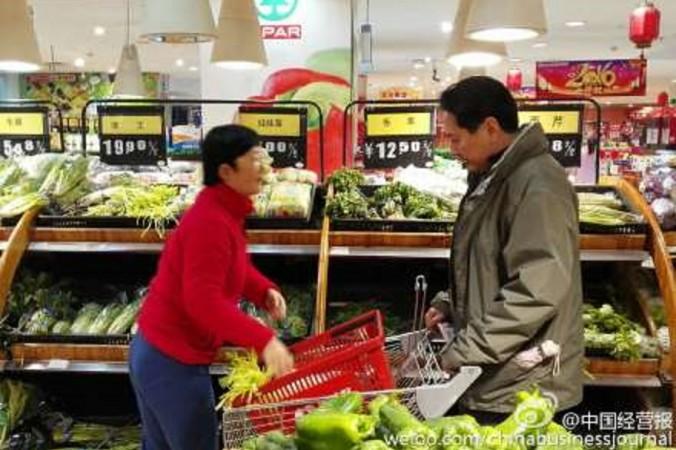 Ли Сяопэн и его жена покупают овощи 12 февраля. Фото: China Business Journal