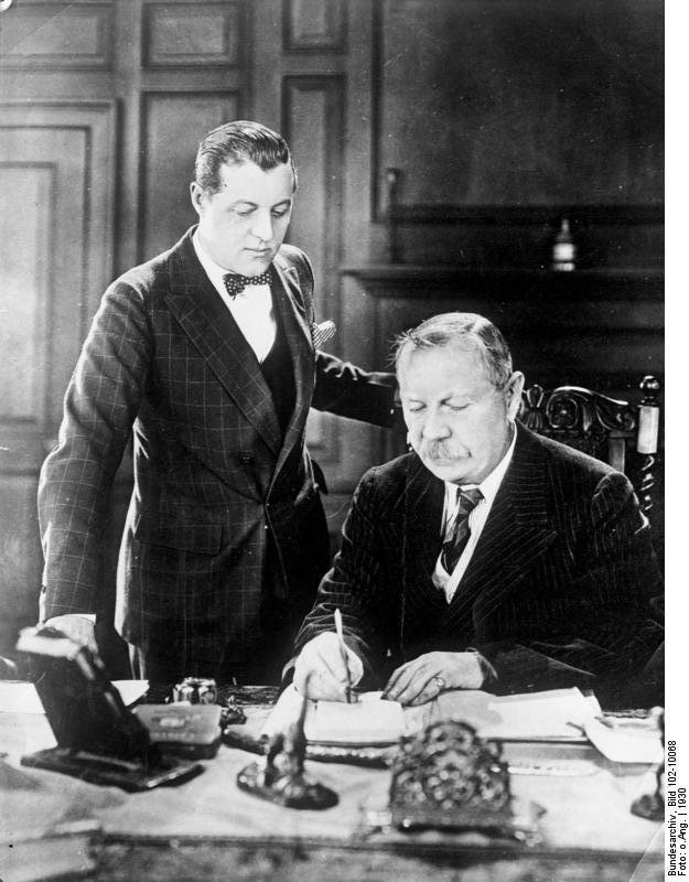 Der berühmte englische Schriftsteller Conan Doyle der berühmte Veter der bekannten Cherlock-Holmes-Romane ist, 71 Jahre alt, in London gestorben. Unser Bild zeigt den berühmten englischen Schriftsteller Conan Doyle bei der Arbeit an seinem Schreibtisch. Stehend sein Sohn Adrian Doyle.