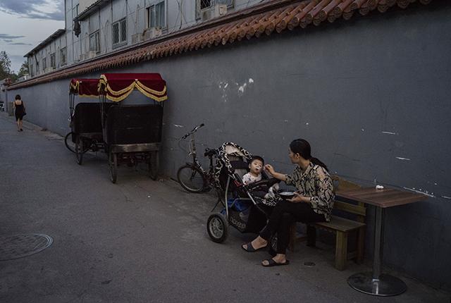 Китаянка кормит сына в ресторане в хутуне ― традиционном закрытом жилом районе 12 июня 2015 г., Пекин, Китай. Фото: Kevin Frayer/Getty Images