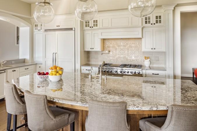 Деревянный пол, белая мебель и мраморная столешницы делают кухню функциональной и никогда не выходящей из моды. Фото: hikesterson/iStock