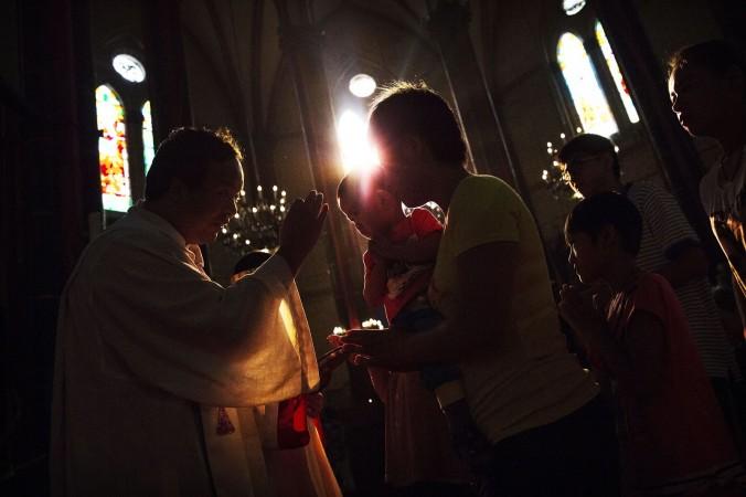 Китайская католичка принимает причастие от священника в церкви в Пекине, Китай, 15 августа 2014 г. Фото: Kevin Frayer/Getty Images