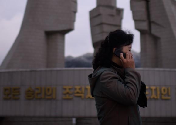 Женщина говорит по телефону у памятника в честь основания партии в Пхеньяне 11 октября 2015 г. Фото: Ed Jones/AFP/Getty Images