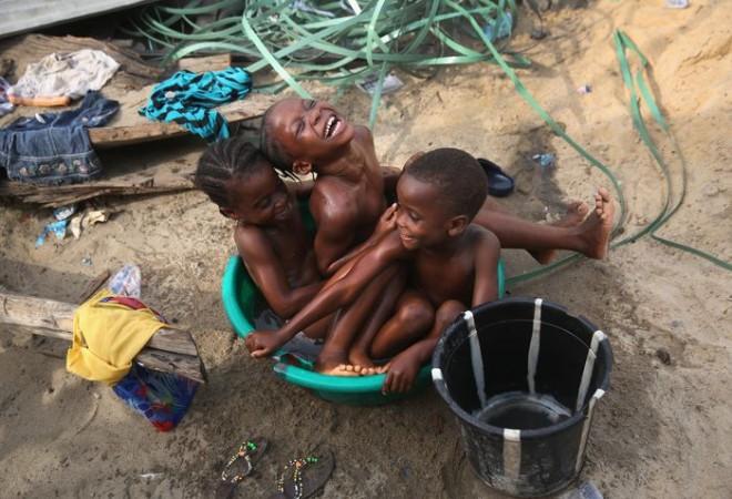 Дети купаются в тазу, трущобы Вест Поинт, Монровия, Либерия, 9 февраля, 2016. Вест Поинт один из самых бедных и перенаселённых районов Либерии. Район сильно пострадал от лихорадки Эбола. После двух лет борьбы с Эболой, 14 января 2016 года Всемирная организация здравоохранения  объявила, что эпидемия закончилась. Фото: John Moore/Getty Images