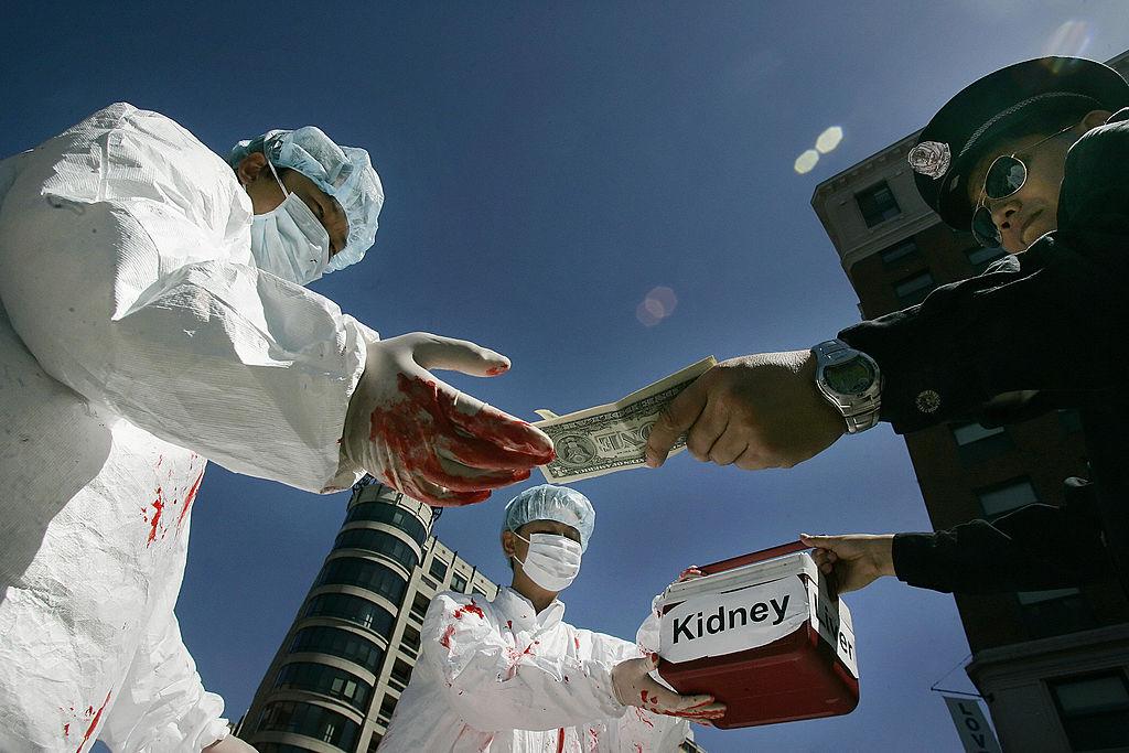 Последователи Фалуньгун демонстрируют акт передачи денег за извлечение органов у узников совести в Китае. Вашингтон, 12 апреля 2006 года. Фото: JIM WATSON/AFP/Getty Images)