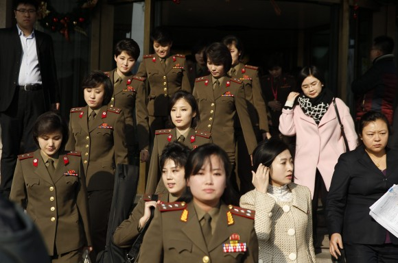 Участницы северокорейской группы Moranbong уходят из своего отеля в Пекине 11 декабря. Фото: STR/AFP/Getty Images