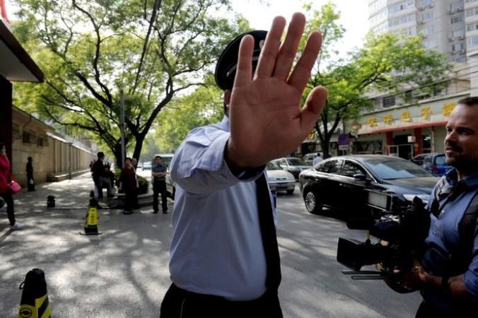 Китайский милиционер запрещает журналистам фотографировать. Фото: RALSTON/AFP/Getty Images
