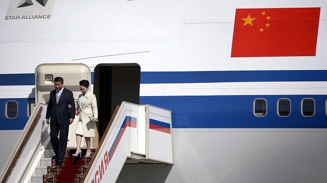 Председатель КНР Си Цзиньпин и его жена Пэн Liyuan спускаются по трапу самолёта.  Фото:  ALEXANDER NEMENOV/AFP/Getty Images