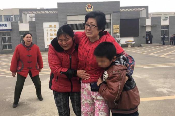 Ли Чжэнцин (в центре) с приёмным сыном и его биологической матерью покидает женскую тюрьму Чанчжоу. Фото: Beijing Times
