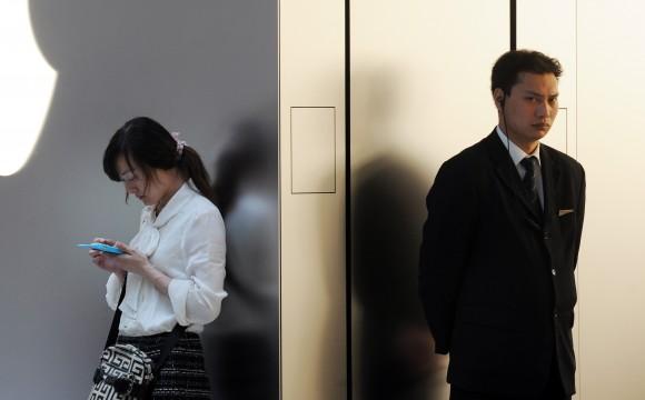 Женщина говорит по мобильному телефону у магазина Apple в Шанхае, 7 мая 2012 г. Фото: PETER PARKS/AFP/Getty Images