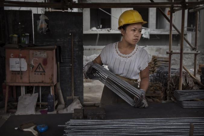 Девушка на стройке в Пекине, 29 августа 2014 г. Фото: Kevin Frayer/Getty Images