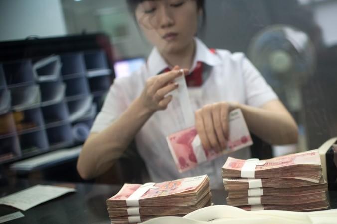 Работница филиала Промышленно-коммерческого банка Китая (ICBC) подсчитывает деньги, обслуживая клиента. 24 сентября 2014 г. Фото: JOHANNES EISELE/AFP/Getty Images
