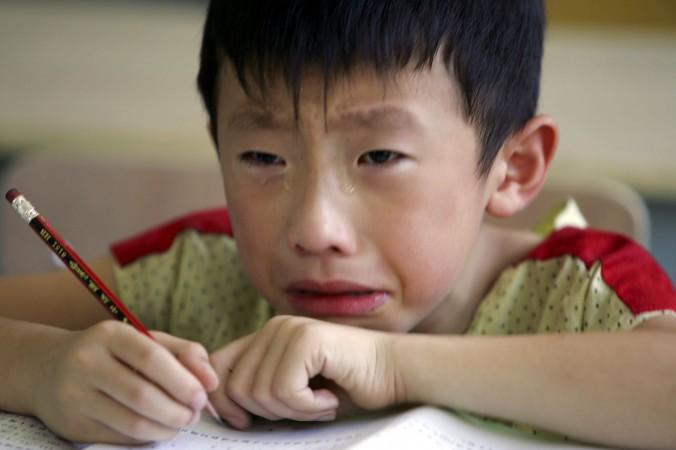 Мальчик плачет от тоски по матери в обучающем центре в Ханчжоу, Китай, 2 августа 2006 г. Фото: Cancan Chu/Getty Images