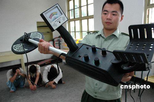 Милиционер демонстрирует металлический детектор, использованный тремя расхитителями, арестованными в июле 2007 г. Фото: Sohu