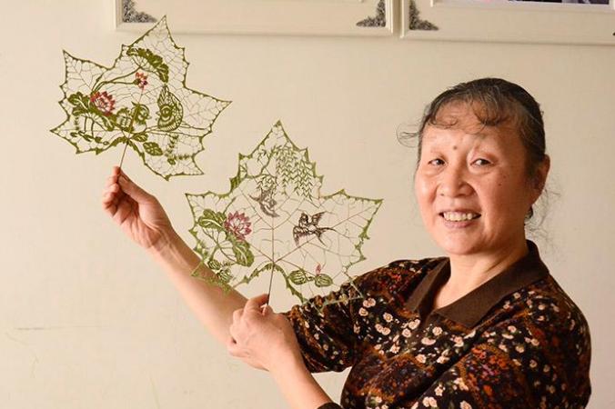 Ду Ваньли и две работы, вырезанные на кленовых листьях. Фото: People's Daily