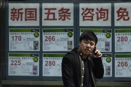 Китаец говорит по мобильному телефону перед агентством по торговле недвижимостью в Пекине, 15 апреля 2013 г. Фото: Wang Zhao/AFP/Getty Images