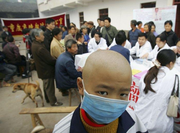 Мальчик в маске с диагнозом «лейкоз» ожидает проверки специалистами, «раковая деревня» Чунцин, Китай. Фото: China Photos / Getty Images