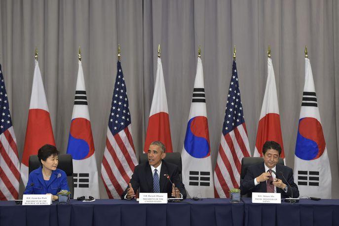 Президент США Барак Обама принимает участие в трехсторонней встрече с премьер - министром Японии Синдзо Абэ и президентом Южной Кореи Пак Кын Хе. Фото: MANDEL NGAN/AFP/Getty Images