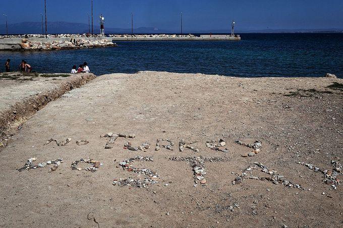 Надпись галькой гласит «ни Турция, ни оставаться». надпись расположена недалеко от лагеря беженцев суда на греческом острове Хиос. Фото: LOUISA GOULIAMAKI/AFP/Getty Images