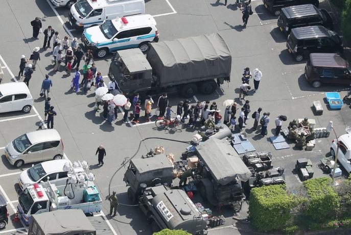 Люди стоят в очереди к полевой кухне. Фото: JIJI PRESS/AFP/Getty Images