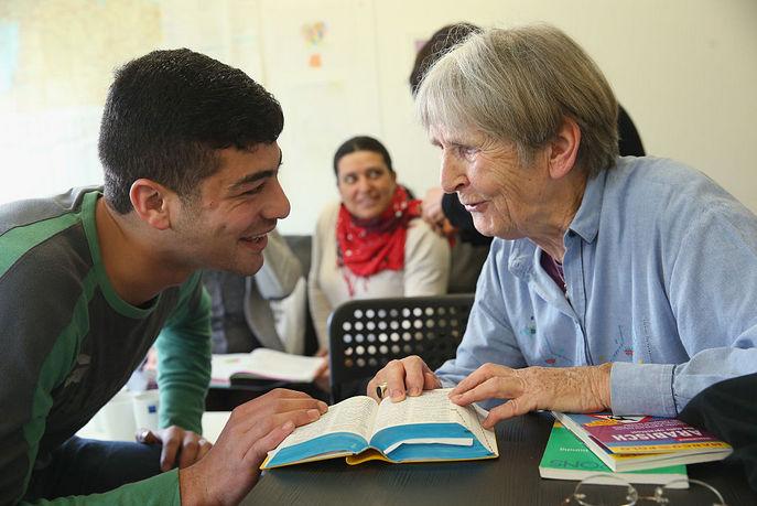 Сирийский беженей Имад Авад разговаривает с помощью немецко-арабского словаря с местным волонтёром, которые приходя два раза в неделю в приют для беженцев в Берлине в рамках интеграции. Местные жители, многие из которых пенсионеры, ходят в приют на регулярной основе, чтобы помочь беженцам. Фото: Sean Gallup/Getty Images