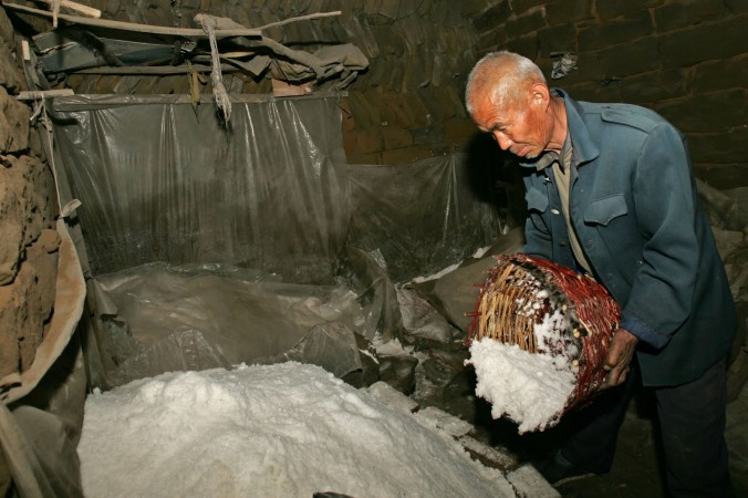 Рабочий насыпает соль 31 марта 2006 года, провинция Шэньси, Китай. Фото: China Photos/Getty Images