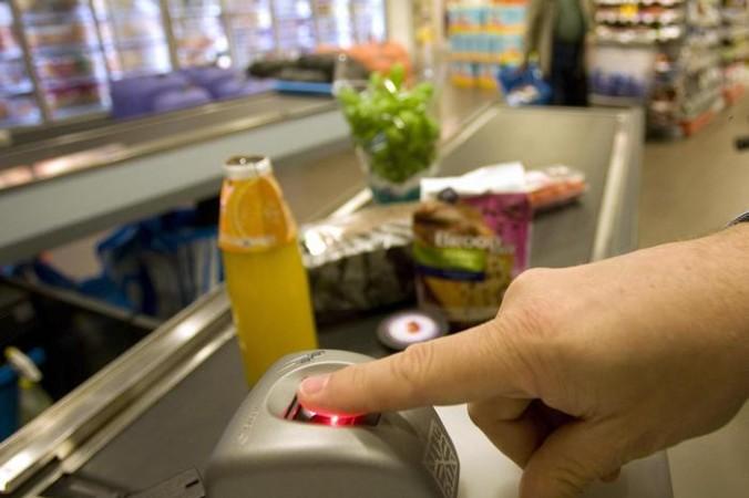 Идентификация покупателя по отпечаткам пальцев. Фото: Sander KONING/AFP/Getty Images