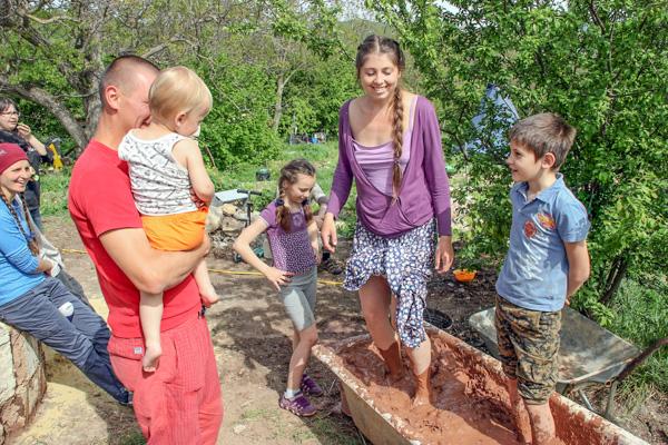 Всей семьёй делаем печь: Сергей с сынишкой на руках, дочь Катя (в центре), мама Рая (месит саман). Фото: Алла Лавриненко/Великая Эпоха