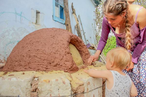 Раиса с сыном — мастер-класс по строительству саманной печи продолжается. Фото: Алла Лавриненко/Великая Эпоха