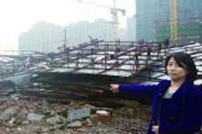 Г-жа Ши стоит рядом со своим разрушенным домом. Фото: via Modern Express