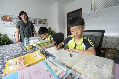 Хэ Идэ (справа) выполняет домашнее задание. Фото: Modern Express