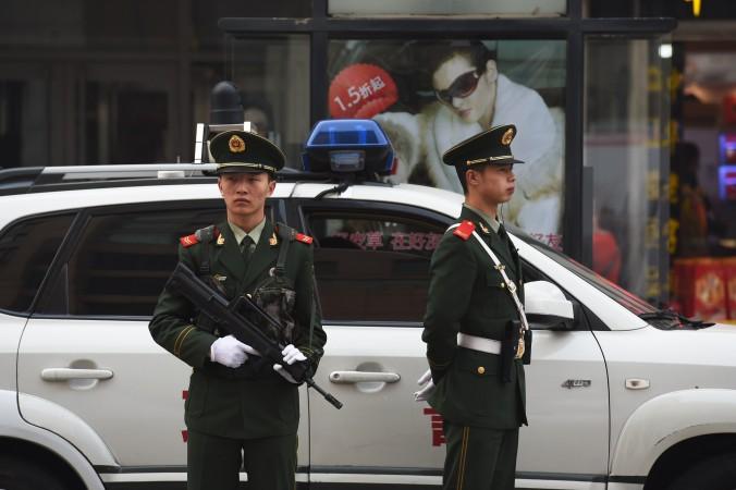 Китайская военизированная полиция наблюдает за прохожими в торговом районе Ванфуцзин в Пекине 24 октября 2014 г. Фото: Greg Baker/AFP/Getty Images)