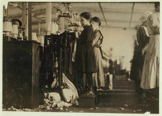 Эта маленькая девочка должна стоять на подставке, чтобы дотянуться до вязального станка. Штат Теннесси, декабрь 1910 года. Фото: L.W. Hine/LOC