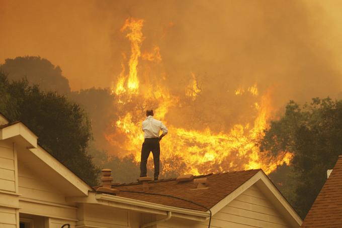 Житель дома смотрит на приближающийся пожар. Фото: David McNew/Getty Images