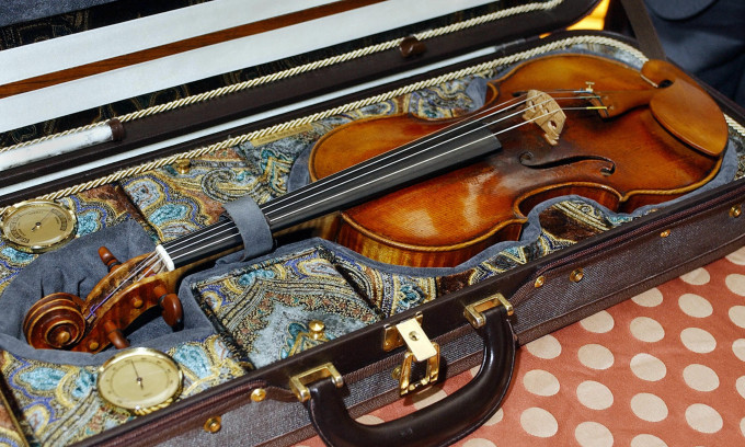 "NEW YORK, UNITED STATES: The ""Il Cannone"" violin owned by Italian composer Niccolo Paganini is displayed at a press conference, 03 November, 2003, in New York. American jazz violinist Regina Carter will play the violin, made by Italian Giuseppe Guarneri in 1743, at a concert, 03 November, at Lincoln Center in New York. Carter became the first jazz musician -- and the first African American -- to play the instrument when, as a gesture of solidarity after the September 11, 2001 terrorist attacks, she was invited to perform in Genoa, Italy. AFP PHOTO/Stan HONDA (Photo credit should read STAN HONDA/AFP/Getty Images)"