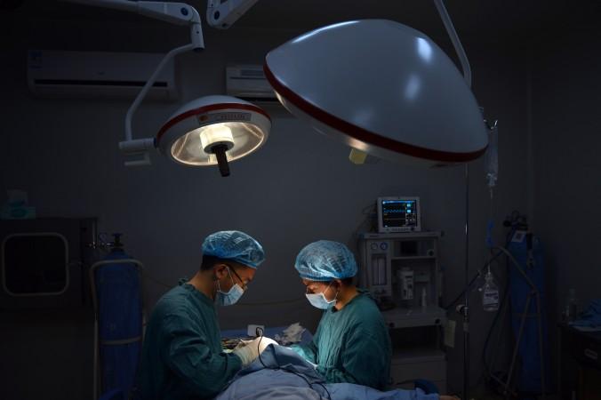Пластический хирург Ван Сюмин делает операцию по коррекции носа, г. Чунчин, 9 августа 2013 г. Фото: Peter Parks/AFP/Getty Images