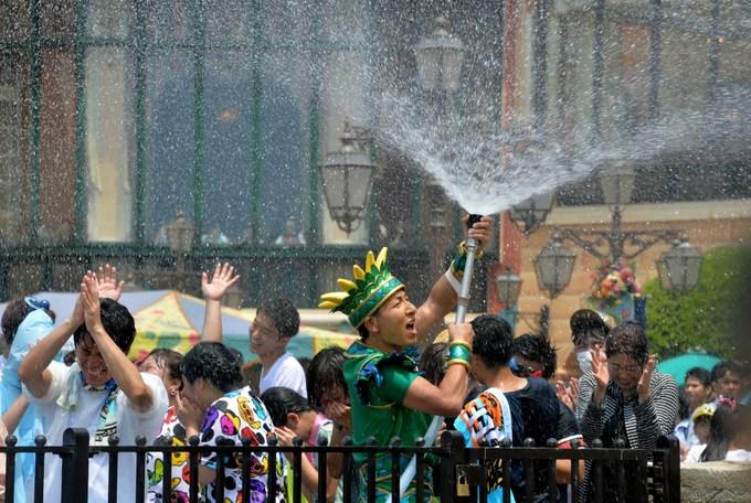 Работник Диснейленда в Токио обливает посетителей водой, чтобы спасти от 35-градусной жары. Фото: YOSHIKAZU TSUNO/AFP/Getty Images