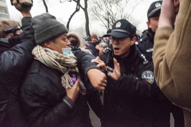 Милиционер отталкивает журналистов и сторонников правозащитника Пу Чжицяна у здания второго народного суда в Пекине 14 декабря 2015 г. Фото: FRED DUFOUR/AFP/Getty Images
