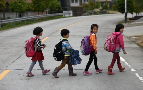 Пэн идёт по улице с учениками из её школы. Фото: via Xinhua