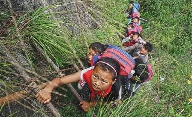 Школьники из отдалённой китайской деревни карабкаются по вертикальной скале, чтобы попасть в школу