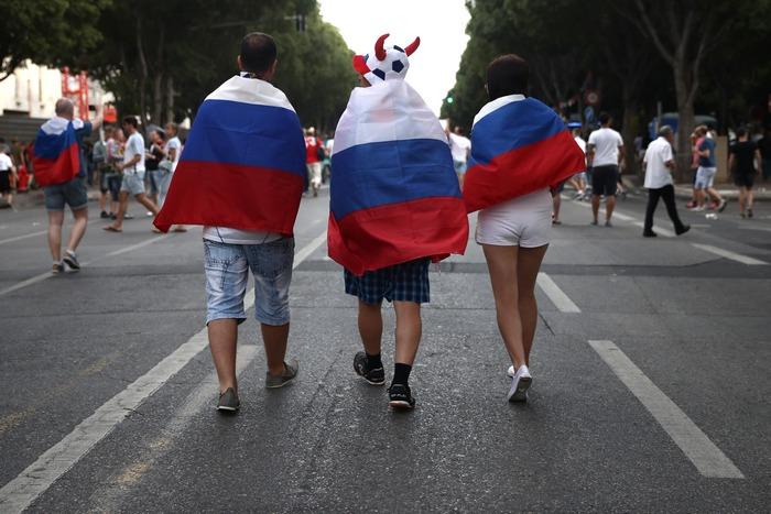 Российские болельщики, накрытые своим национальным флагом, идут по улице перед игрой своей сборной против Англии в тот же день. 11 июня 2016 года, Марсель. Футбольные болельщики со всей Европы съехались во Францию на футбольный турнир Евро-2016 УЕФА. Фото: Carl Court/Getty Images