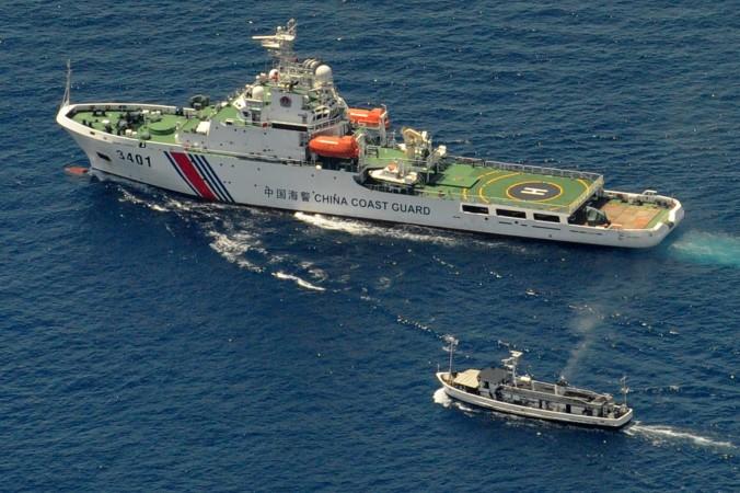 Китайское судно береговой охраны (сверху) и филиппинское грузовое судно, 29 марта 2014 г. Оба судна направляются к отдалённому атоллу в Южно-китайском море, на который претендуют обе страны. Фото: Jay DirectoJ/AFP/Getty Images