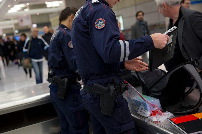 Сотрудники охраны досматривают вещи пассажиров в аэропорту Шарль де Голль. KENZO TRIBOUILLARD/AFP/Getty Images)