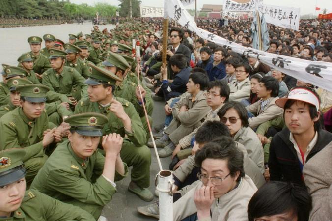 Несколько сот патриотично настроенных студентов сидят рядом с полицейскими у Дома народных собраний на площади Тяньаньмэнь в Пекине 22 апреля 1989 г. Фото: Catherine Henriette/AFP/Getty Images