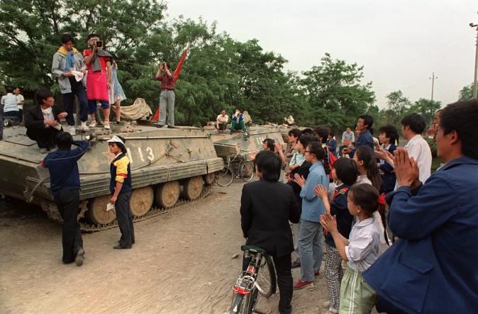 Демонстранты аплодируют студентам, которые стоят на бронетраснпортёрах в Пекине 21 мая 1989 г. студенты пытались убедить солдат не подчиняться военному положению, которое ввели днём раньше. Фото: Catherine Henriette/AFP/Getty Images