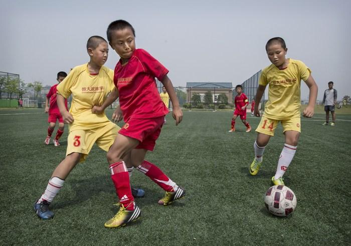 Дети играют в футбол на тренировочном поле в Международной футбольной школе Evergrande в китайской провинции Гуандун. Китай собирается построить более 20 тысяч футбольных школ, чтобы поднять свой международный авторитет. Фото: Kevin Frayer/Getty Images