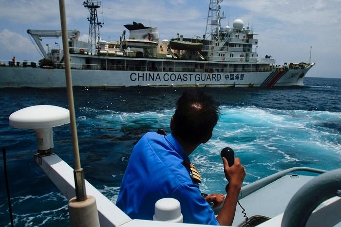 Китайские «голубые человечки» в Южно-китайском море. Офицер ВМФ Малайзии переговаривается с китайским судном береговой охраны вблизи Куантана, Малайзия, 15 марта 2014. Фото: Rahman Roslan/Getty Images